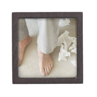 Man's feet surrounded by crumpled tissues premium gift boxes