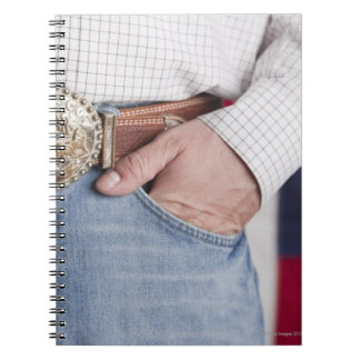 Man's hand in the pocket of his jeans spiral note book