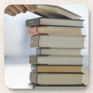 Man's hand taking a book from a stack of books coaster