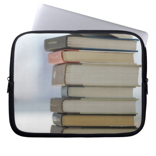 Man's hand taking a book from a stack of books computer sleeves