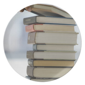 Man's hand taking a book from a stack of books melamine plate
