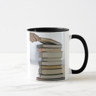 Man's hand taking a book from a stack of books mug