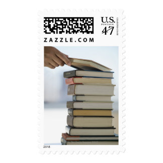 Man's hand taking a book from a stack of books postage