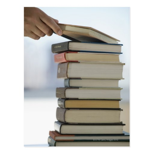 Man's hand taking a book from a stack of books postcard