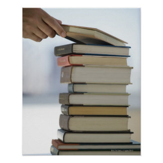 Man's hand taking a book from a stack of books poster