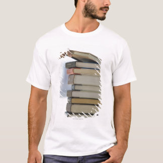 Man's hand taking a book from a stack of books T-Shirt