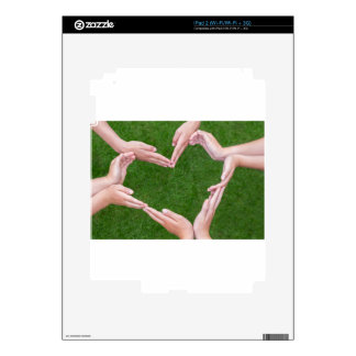 Many arms of children construct heart above grass decals for iPad 2