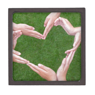 Many arms of children construct heart above grass gift box
