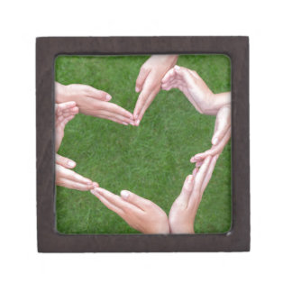 Many arms of children construct heart above grass keepsake box