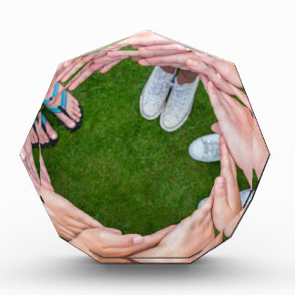 Many arms of children with hands making circle award