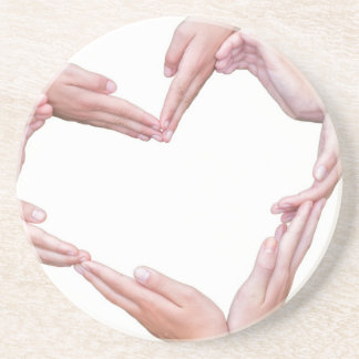 Many arms of girls construct heart on white drink coaster