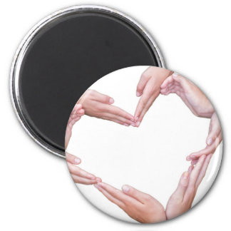 Many arms of girls construct heart on white magnet