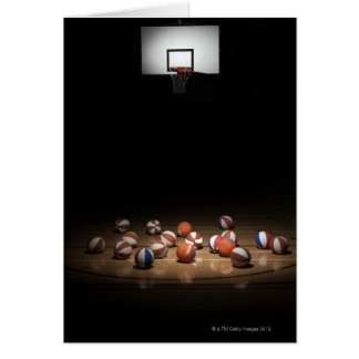 Many basketballs resting on the floor card