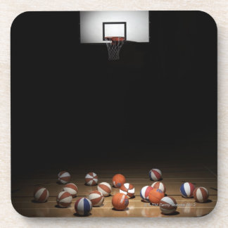 Many basketballs resting on the floor drink coaster