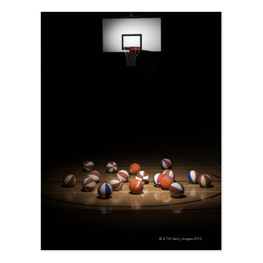 Many basketballs resting on the floor postcard