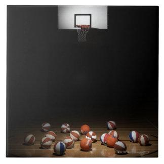 Many basketballs resting on the floor tile