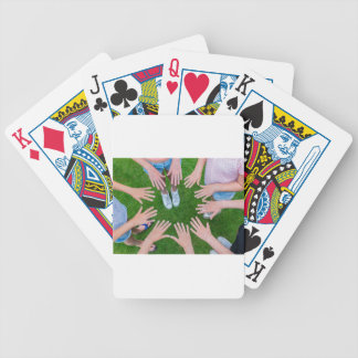 Many children hands joining in circle above grass bicycle playing cards
