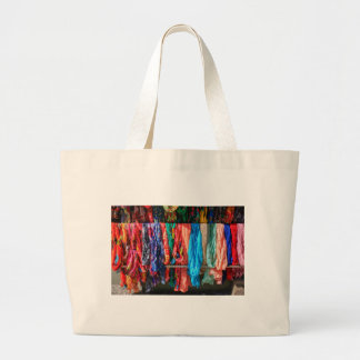 Many colorful scarves hanging at market large tote bag