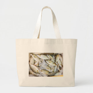 Many small caught dead fish with ice on market large tote bag