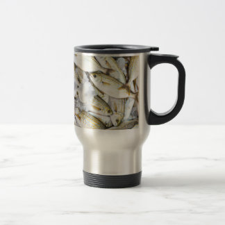 Many small caught dead fish with ice on market travel mug