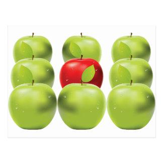 Manzana roja entre manzanas verdes postales