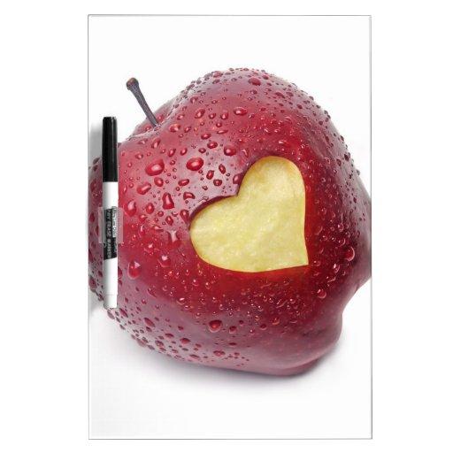 Manzana roja fresca con un símbolo en forma de cor pizarras blancas
