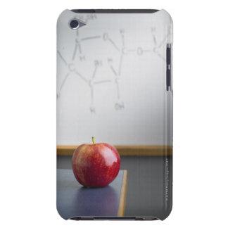 Manzana roja que se sienta en el escritorio de los iPod touch protector