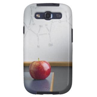 Manzana roja que se sienta en el escritorio de los galaxy SIII carcasa