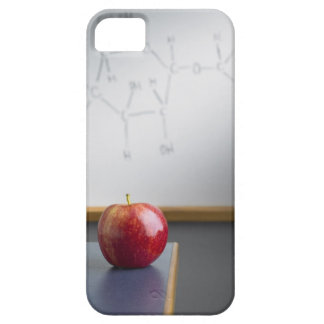 Manzana roja que se sienta en el escritorio de los iPhone 5 cárcasas