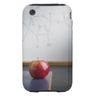 Manzana roja que se sienta en el escritorio de los tough iPhone 3 carcasas