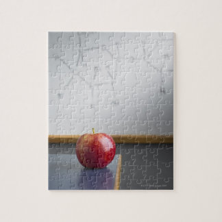 Manzana roja que se sienta en el escritorio de los rompecabeza