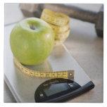 Manzana verde en escala del peso, cinta métrica y azulejo ceramica