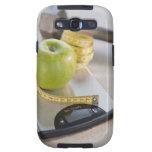 Manzana verde en escala del peso, cinta métrica y galaxy s3 funda