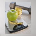 Manzana verde en escala del peso, cinta métrica y poster