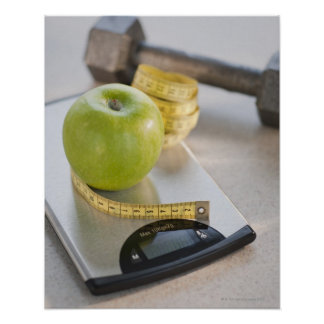Manzana verde en escala del peso, cinta métrica y póster
