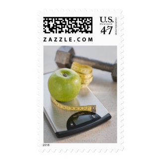 Manzana verde en escala del peso, cinta métrica y sellos postales