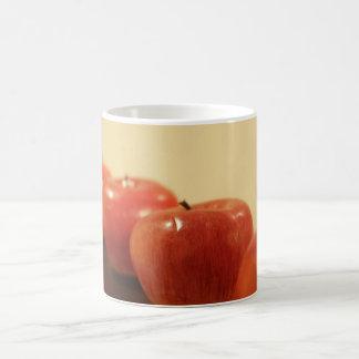 Manzanas rojas en una fila taza clásica