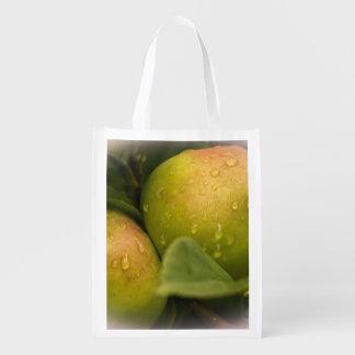Manzanas verdes frescas con las gotitas de agua bolsa para la compra