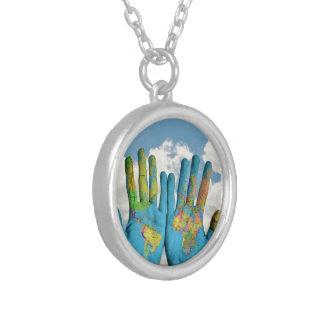 Mapa del mundo pintado colorido en manos, foto del collar plateado