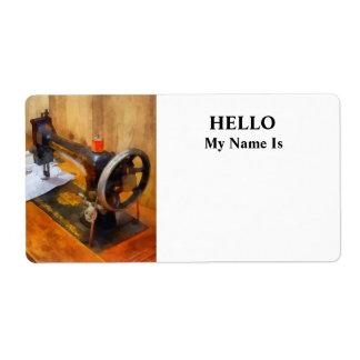 Máquina de coser con el hilo anaranjado etiqueta de envío