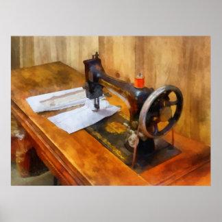 Máquina de coser con el hilo anaranjado póster