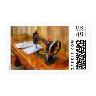 Máquina de coser con el hilo anaranjado sello postal