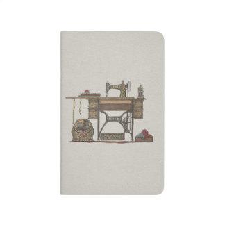 Máquina de coser y gatitos del pedal cuaderno grapado