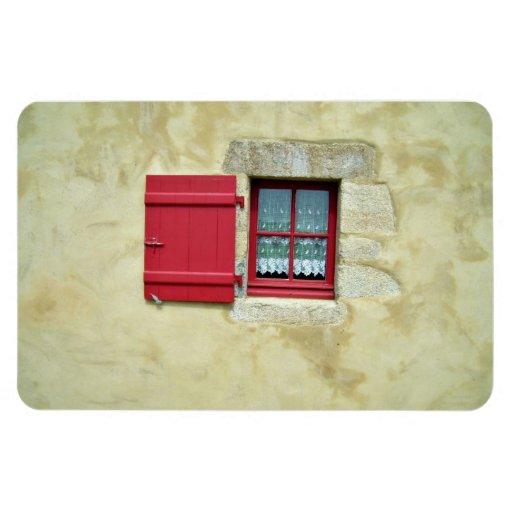 Marco de ventana rojo vibrante en una pared amaril imanes