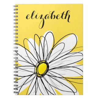 Margarita caprichosa amarilla y blanca con el libros de apuntes con espiral