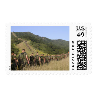 Marines hike their way to a memorial site postage
