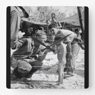 Marines try to soothe a crying child_War Image Square Wall Clock