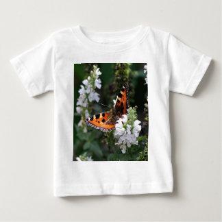 Mariposa anaranjada y negra en las flores blancas polera