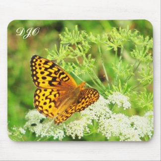 Mariposa anaranjada y negra que descansa sobre la tapetes de raton