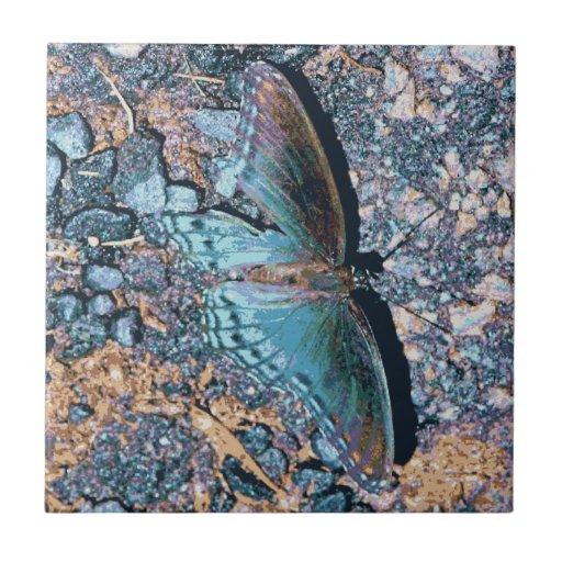 Mariposa azul que descansa sobre el arte de Digita Tejas Ceramicas